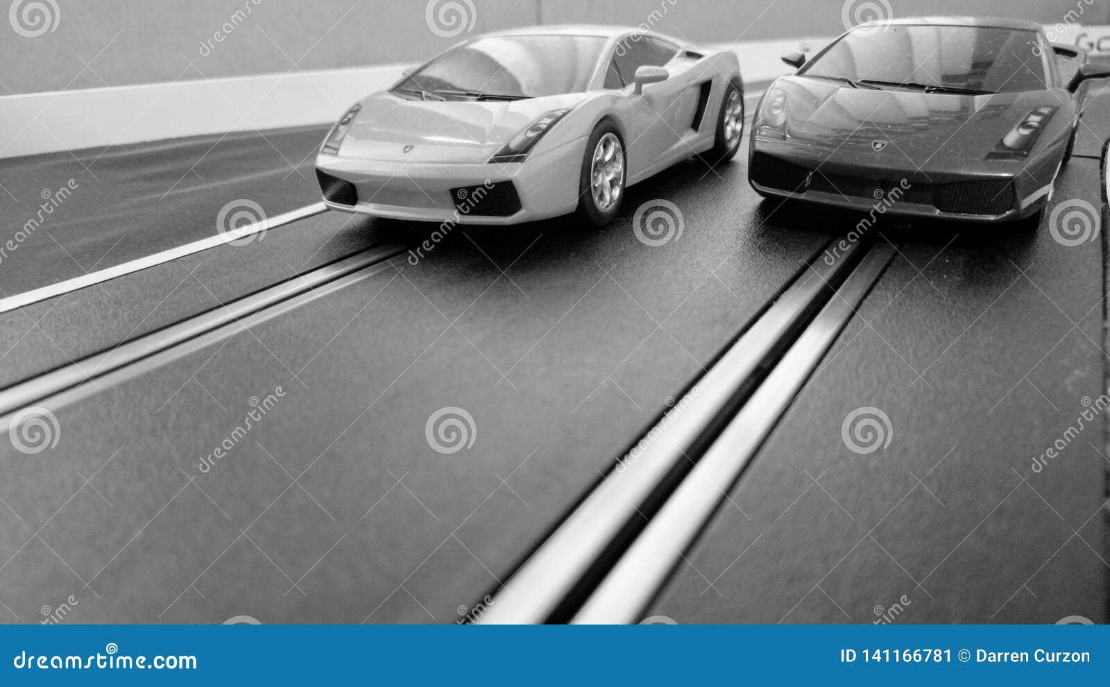 Voitures de course miniature emballant sur une voie de voiture de course miniature, noire et blanche pour un rétro regard