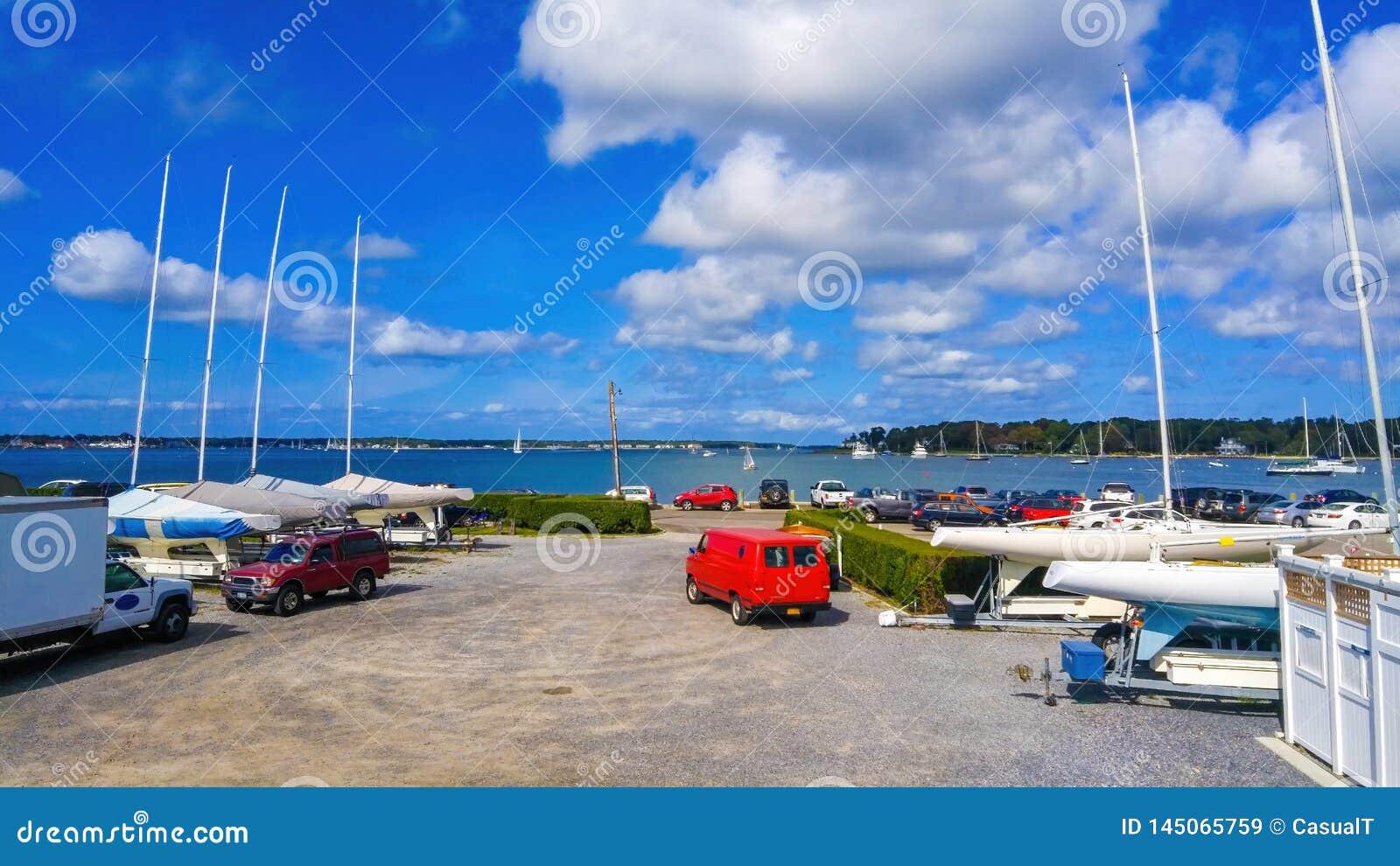 Voitures garées et bateaux amarrés à une marina un jour ensoleillé d été sous un beau ciel bleu