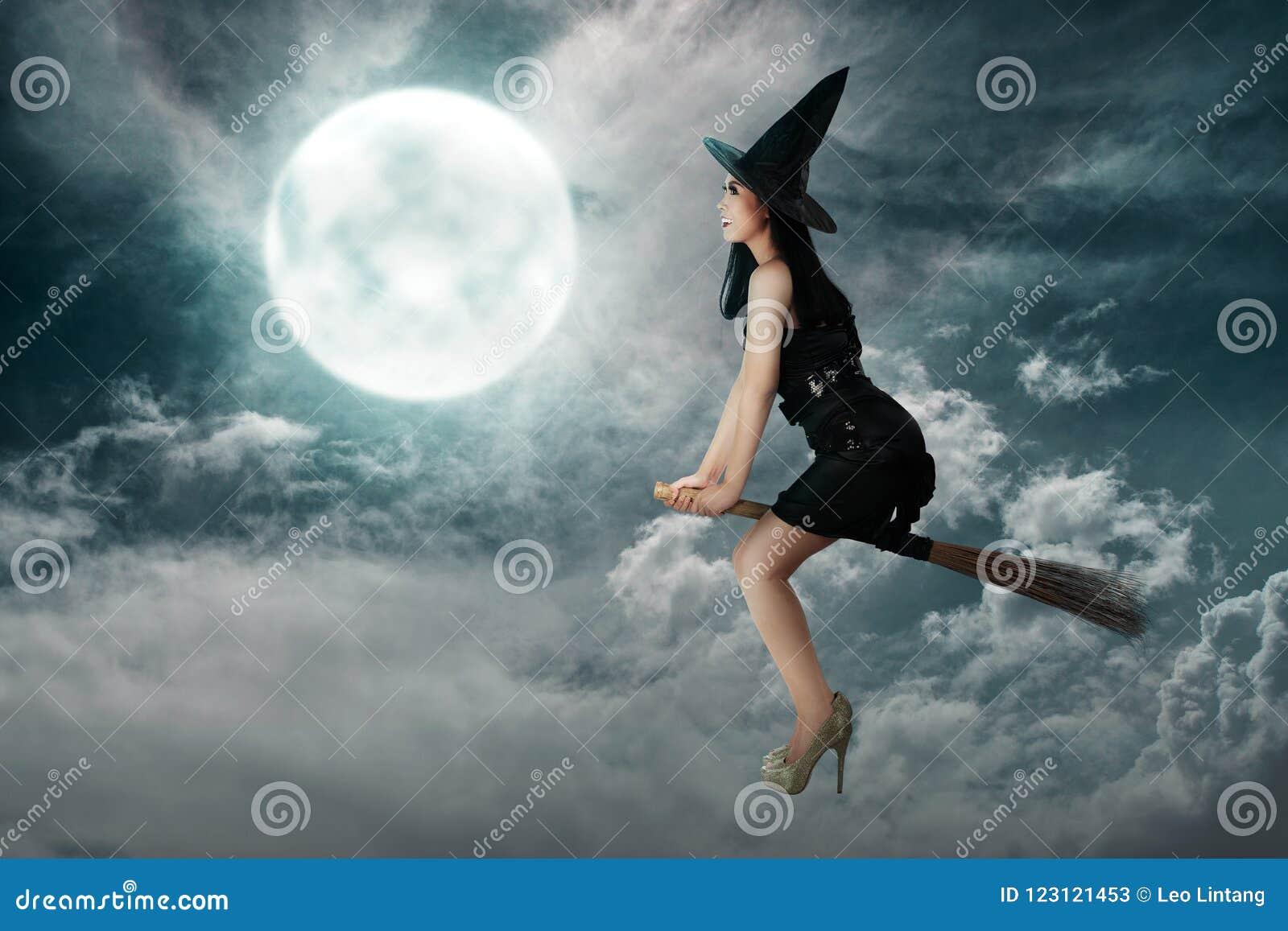 Vol asiatique heureux de femme de sorcière au-dessus d un manche à balai