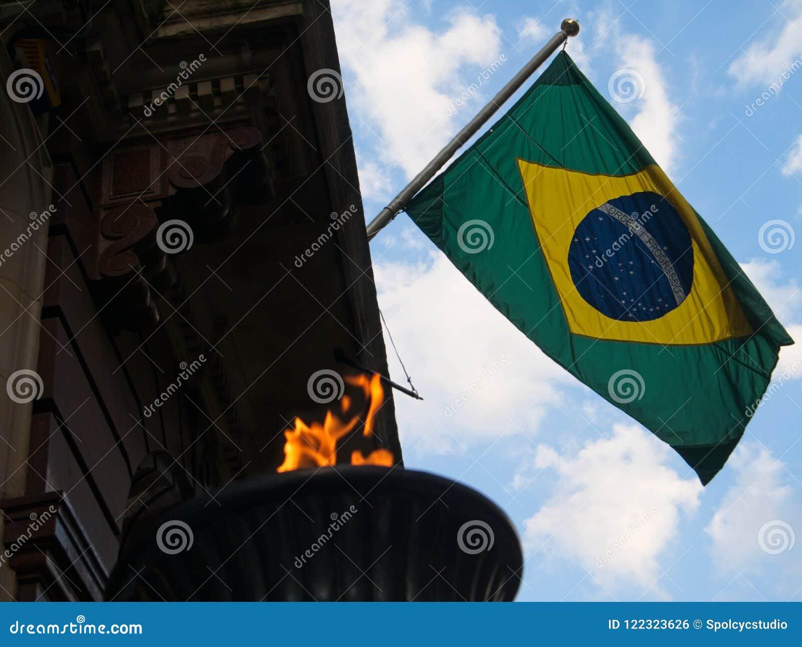 Vol brésilien de drapeau contre le ciel bleu