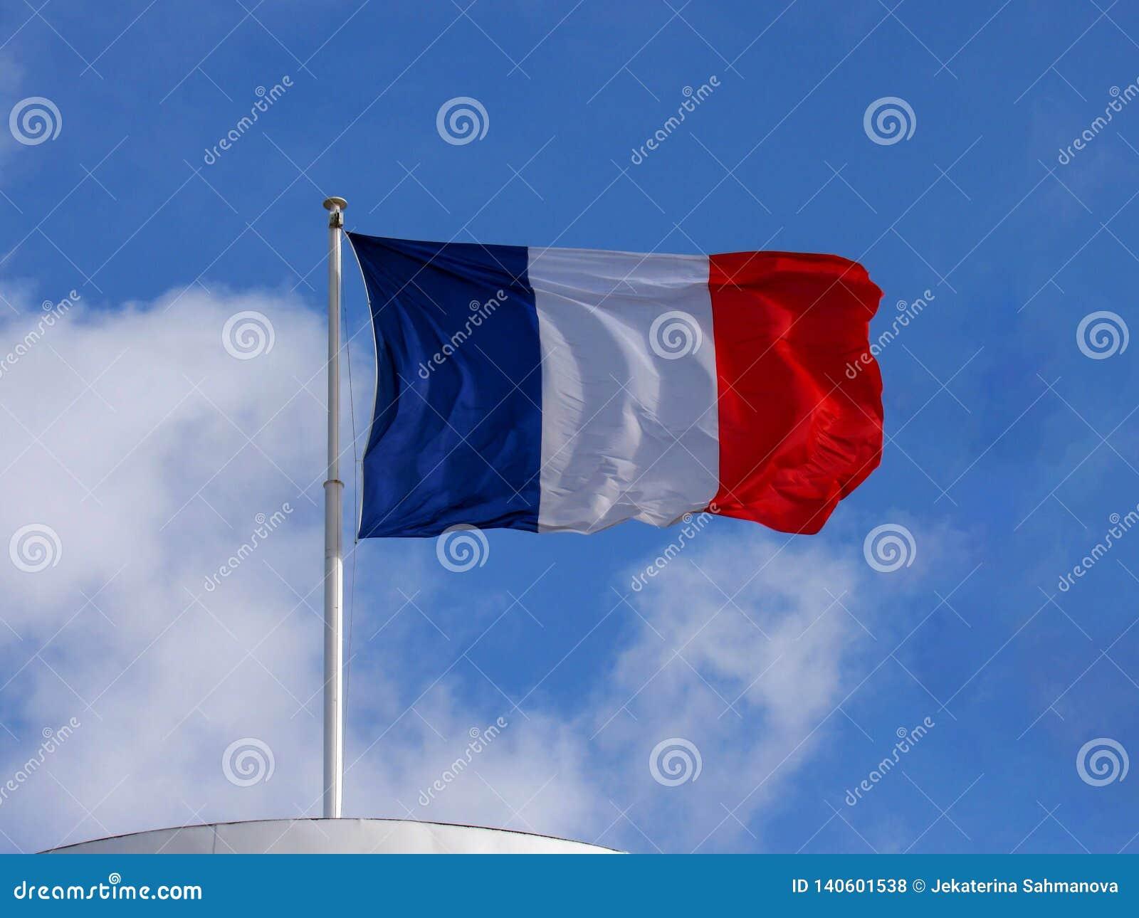 Vol matériel de drapeau de tissu tricolore français dans le fort vent avec l espace de copie avec le fond de ciel bleu