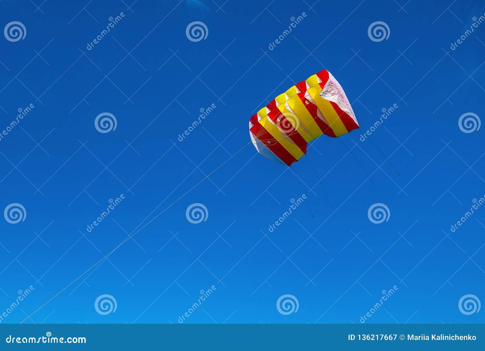 Vol rayé jaune, blanc et rouge de cerf-volant contre un ciel bleu