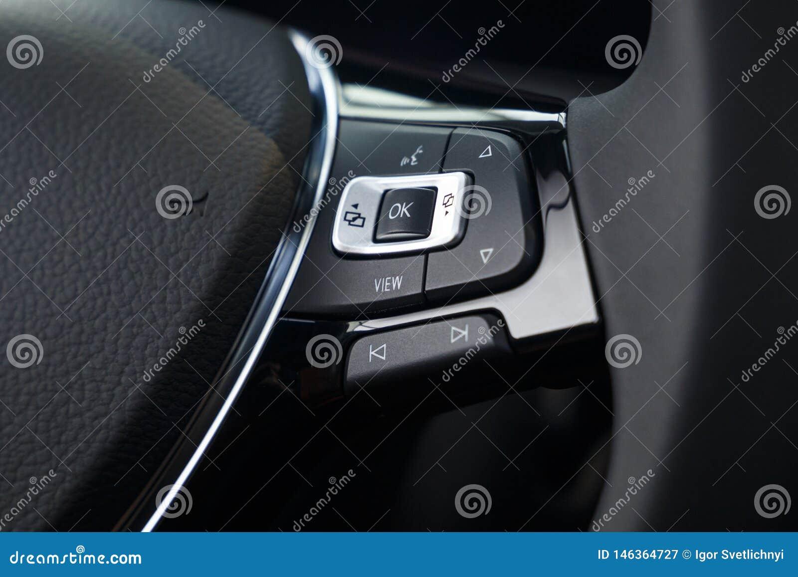 Volante do couro dos multimédios em um carro caro moderno