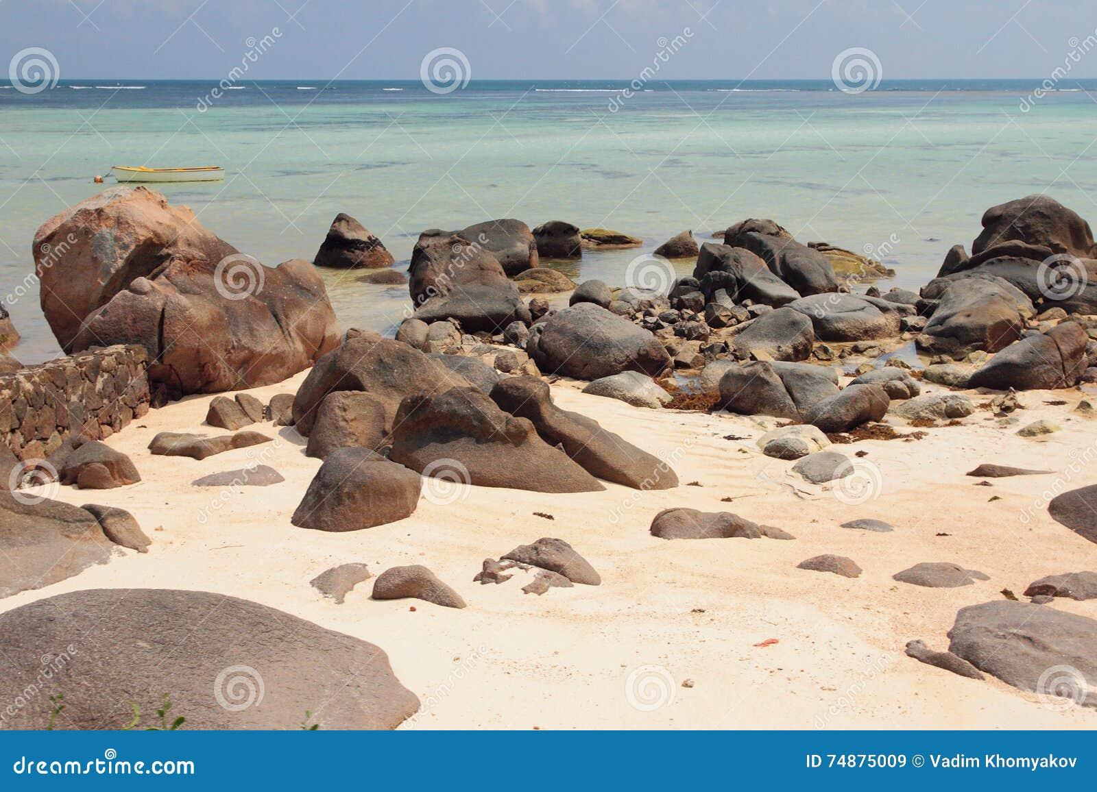 Volcanic boulders and stones on sandy beach. Mahe, Seychelles