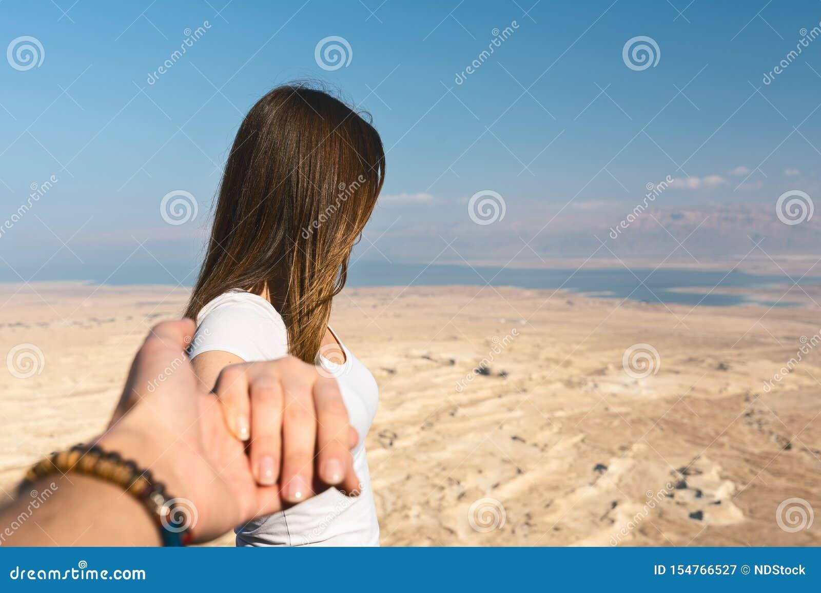 Volg me concept jonge vrouw die de woestijn in Israël kijken