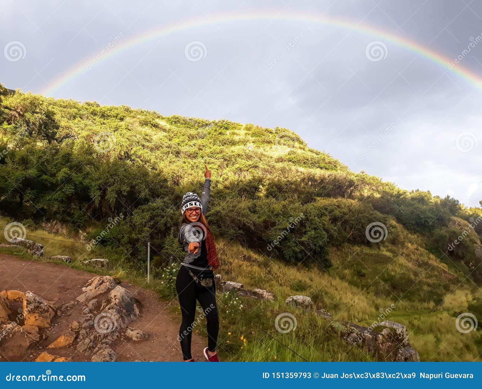 Volg Uw Droomconcept Een langs de weg aan berg lopen en vrouw die regenboog in de hemel kijken