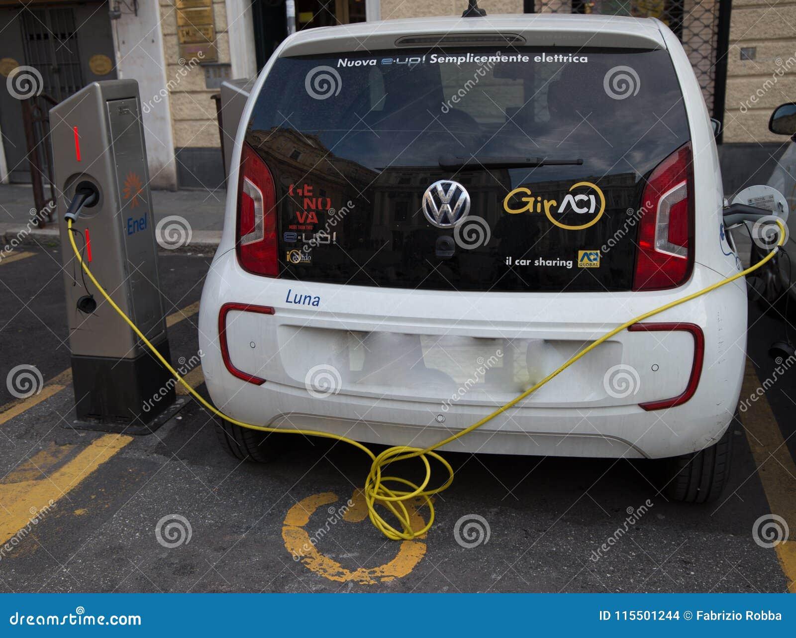 Volkswagen e-Upstår den inkopplingshybrid- elbilen vid uppladdningsstationen, i Genua, Italien