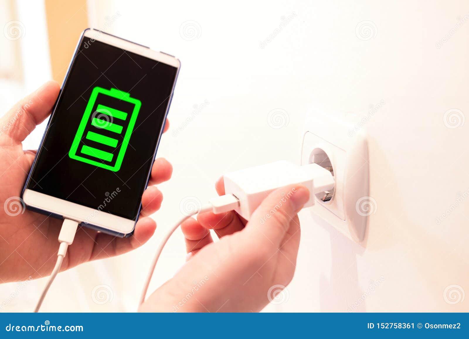 Volle Batterie aufgeladen durch ein Ladegerät Telefon, das von einem Wandausgang auflädt