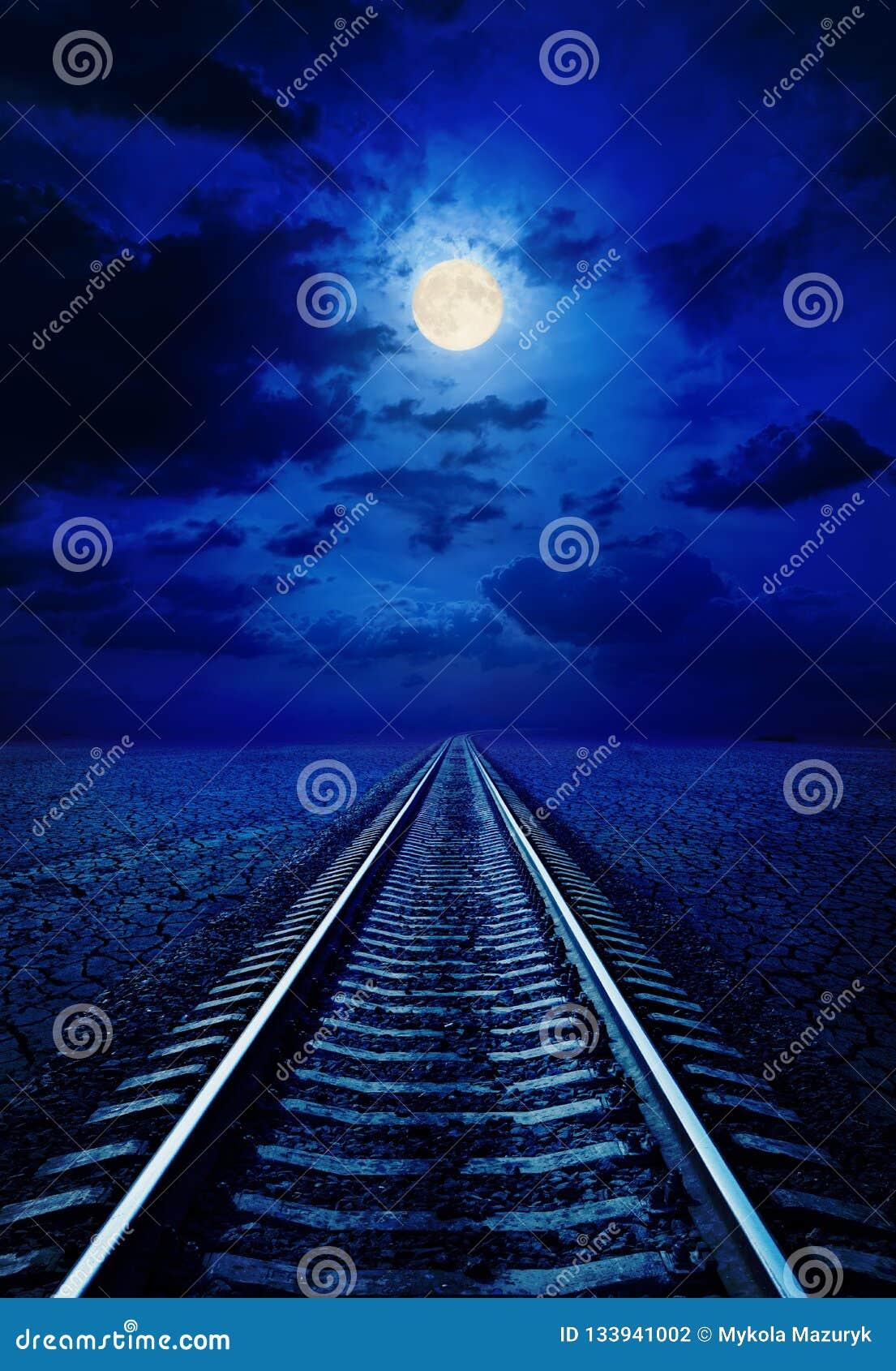 Volle maan in nachthemel met wolken over spoorweg