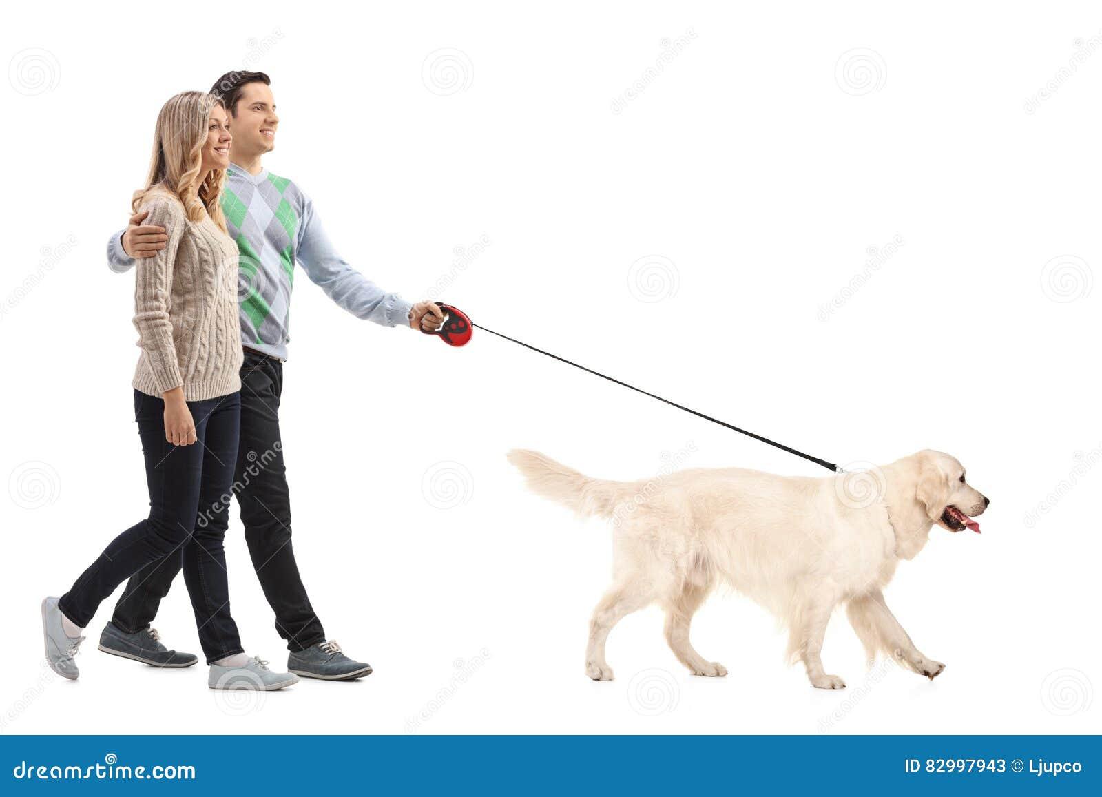 Volledig lengteportret van een gelukkig jong paar die een hond lopen