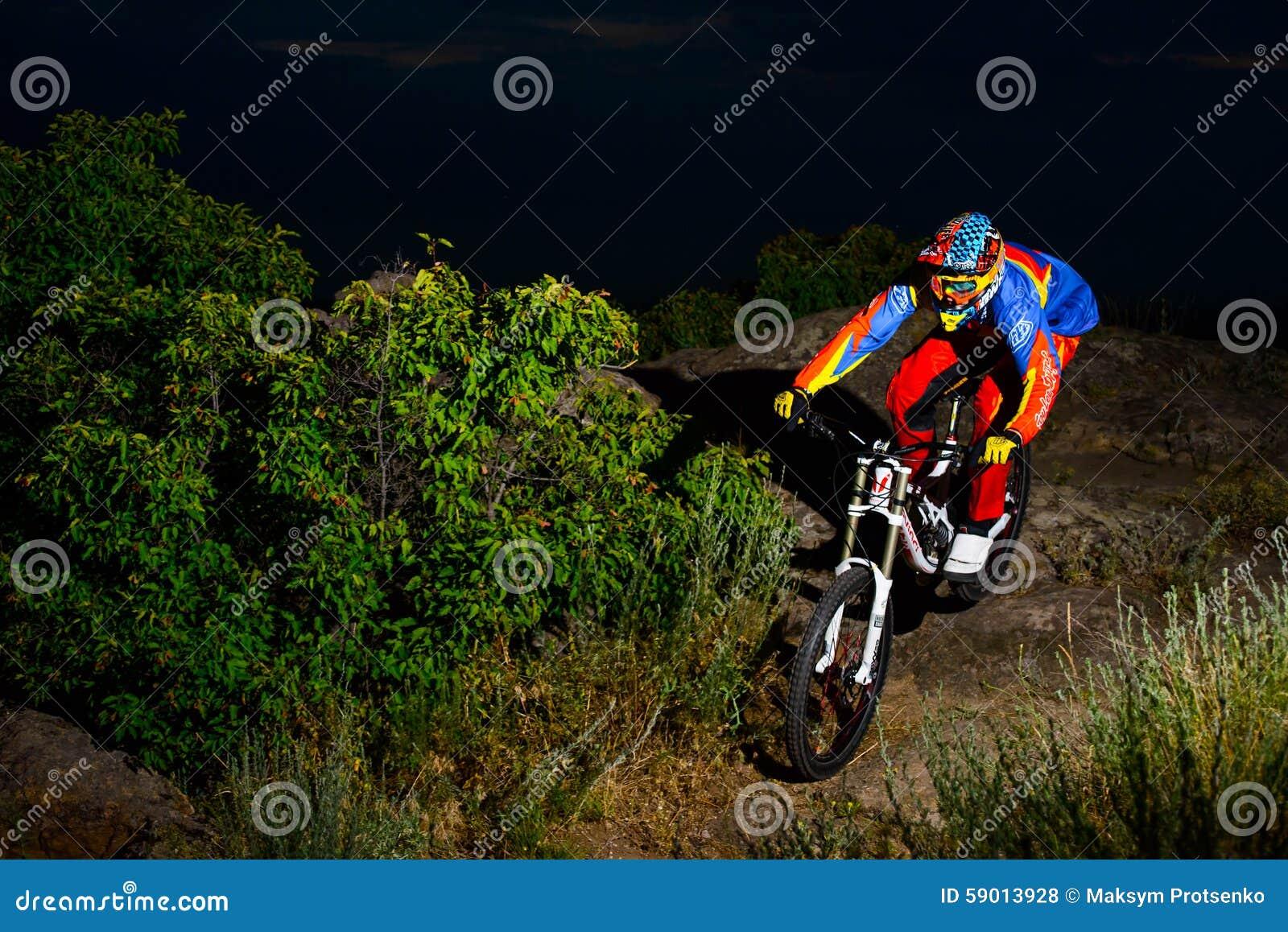 Volledig Uitgeruste Professionele bergaf Fietser die de Fiets berijden op de Nacht Rocky Trail