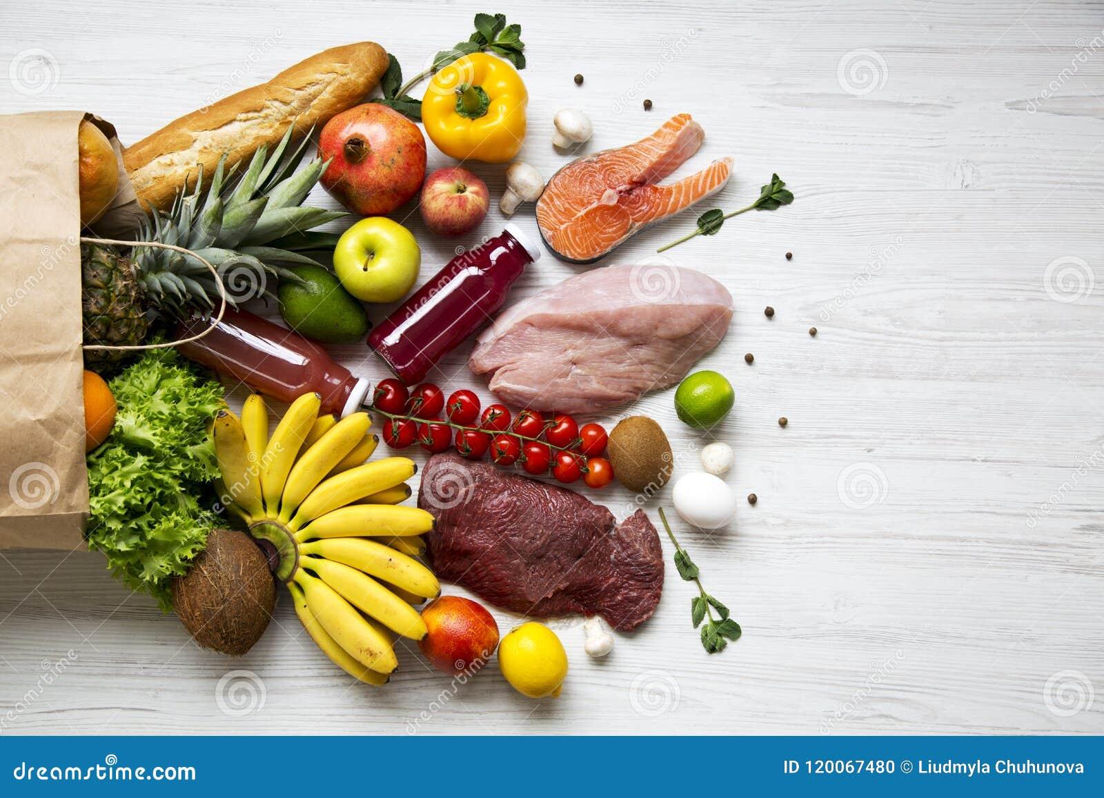 Volledige document zak gezond ruw voedsel op witte houten lijst Kokende voedselachtergrond Vlak-leg van verse vruchten, veggies,