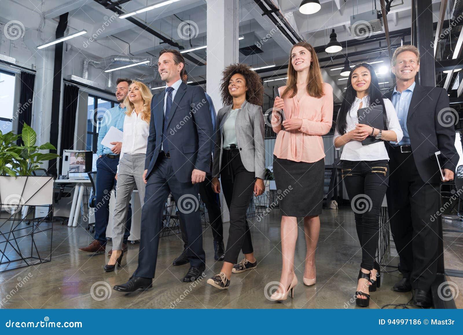 Volledige Lengte Bedrijfsmensen Team Walking In Modern Office, Zekere Zakenlieden en Onderneemsters in Kostuums Divers met