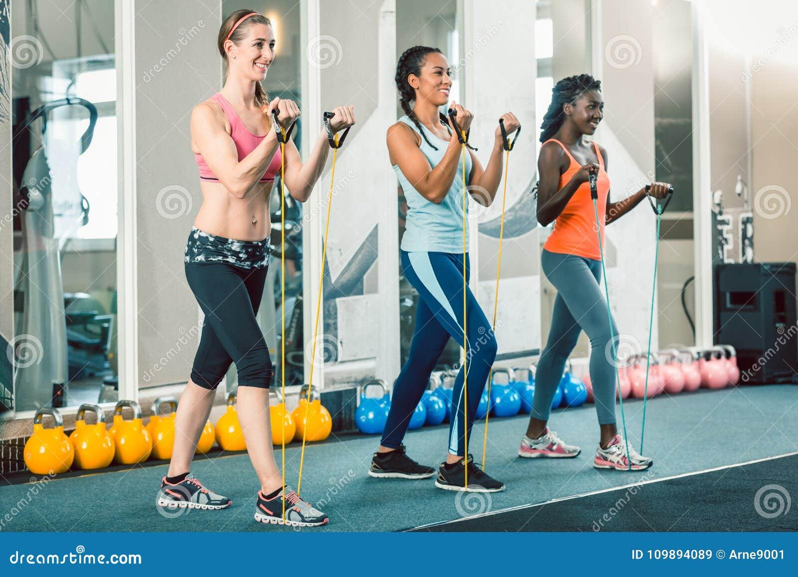 Volledige lengte van drie geschikte vrouwen die met weerstandsbanden uitoefenen