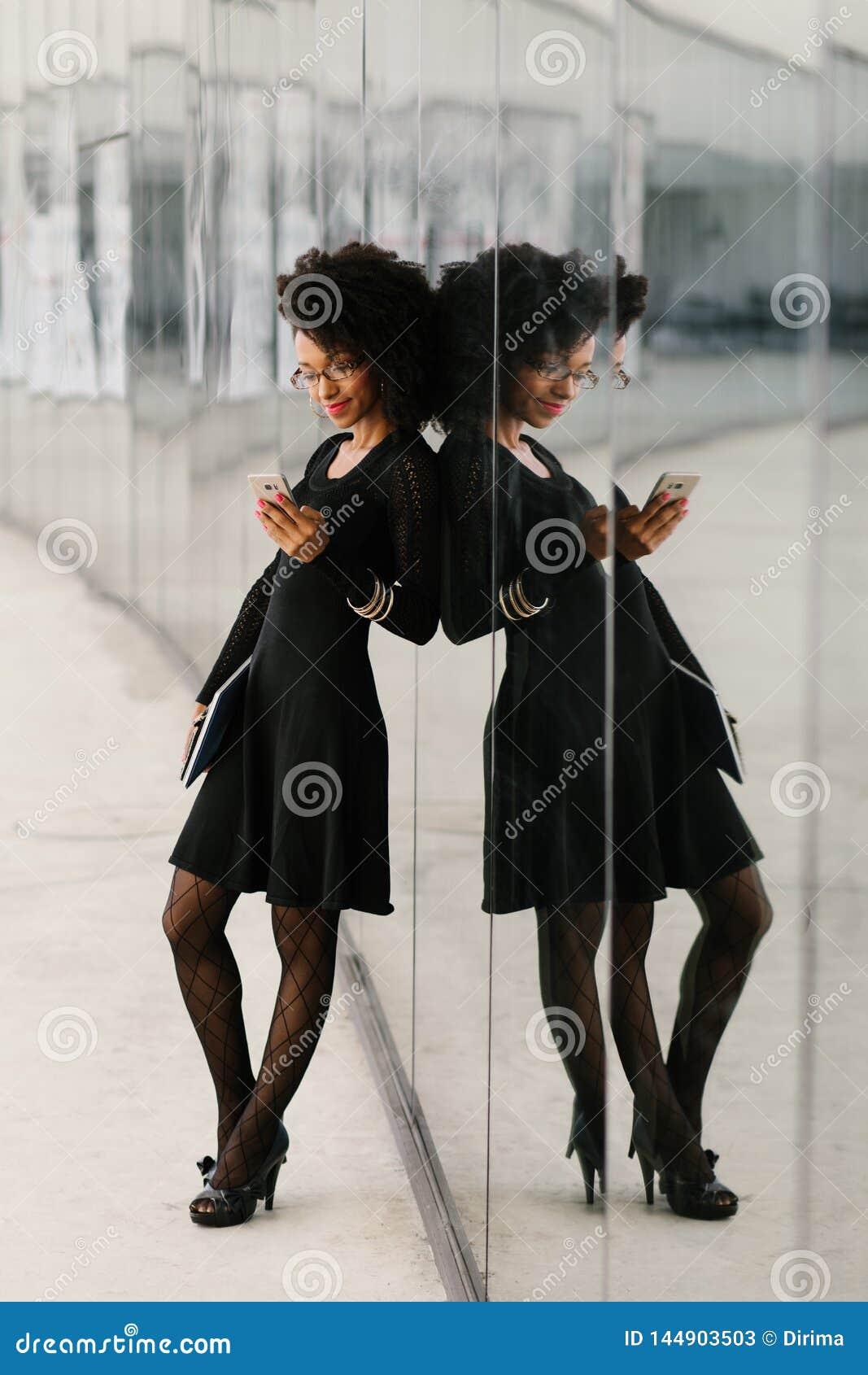 Volledige lengtemening van modieuze onderneemster die cellphone gebruikt