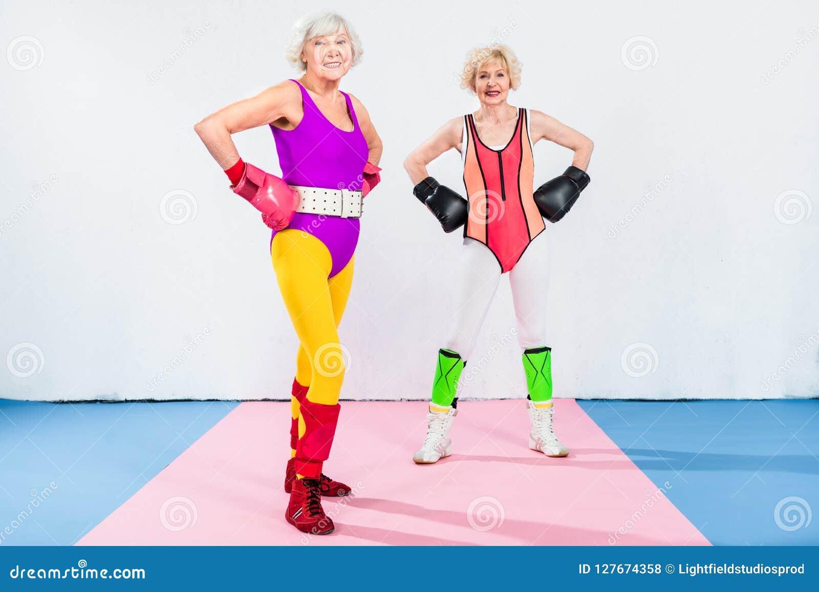 Volledige lengtemening van sportieve hogere dames in bokshandschoenen die zich met handen bij taille en het glimlachen bevinden