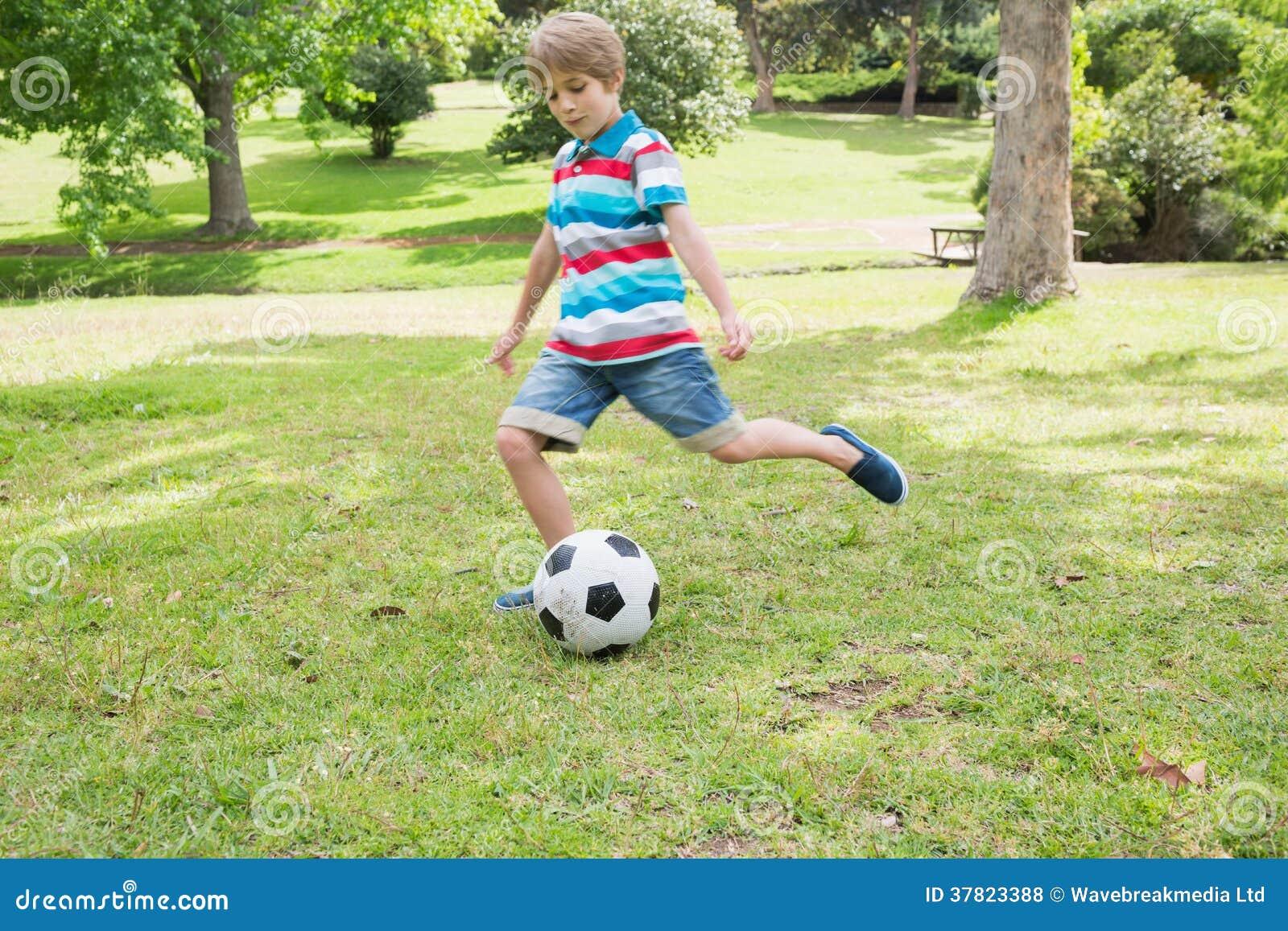 In voller Länge von einem Jungen, der Ball am Park tritt