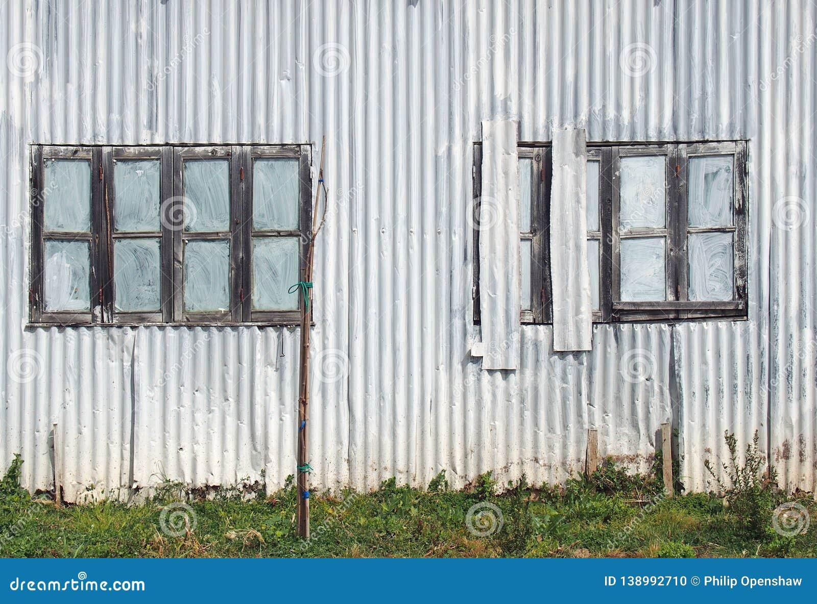 Voller Rahmenabschluß oben eines schäbigen alten verfallenen Wellblechgebäudes mit mit geschlossenem gemalt über ausgebesserten F