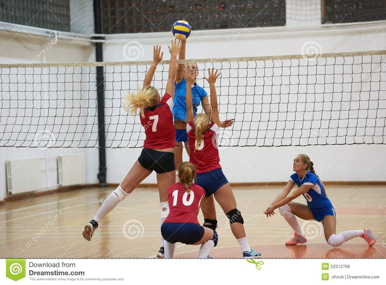 Volleyball game sport with group of young beautiful girls indoor in