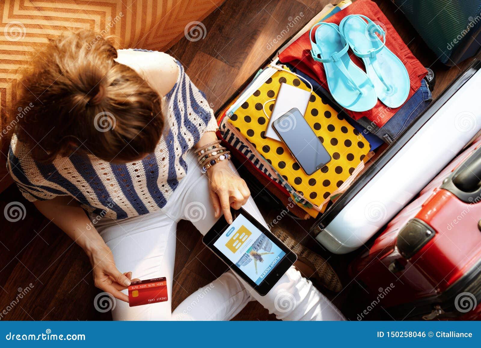 Volo del libro della giovane donna sul PC della compressa vicino alla valigia aperta di viaggio