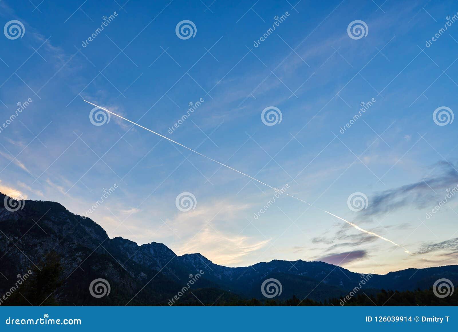 Volo dell aeroplano nel cielo blu fra le nuvole, la luce solare e le montagne al tramonto L Austria, Salzkammergut Alpi austriach