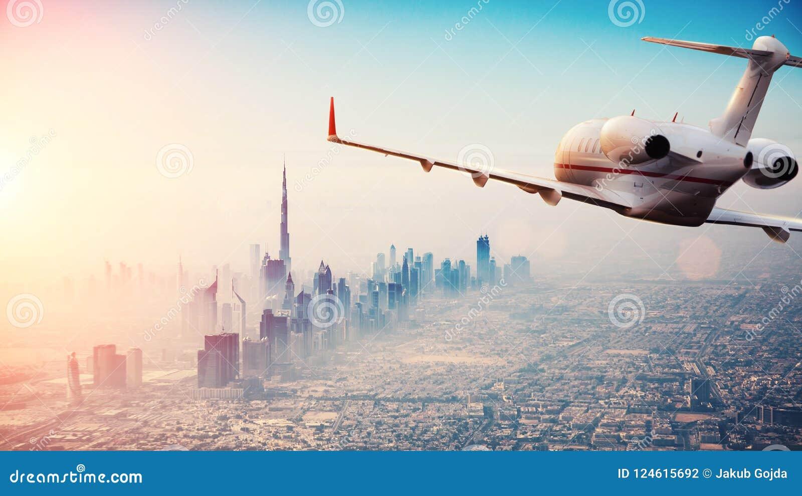 Volo privato dell æreo a reazione sopra la città del Dubai in bello Li di tramonto
