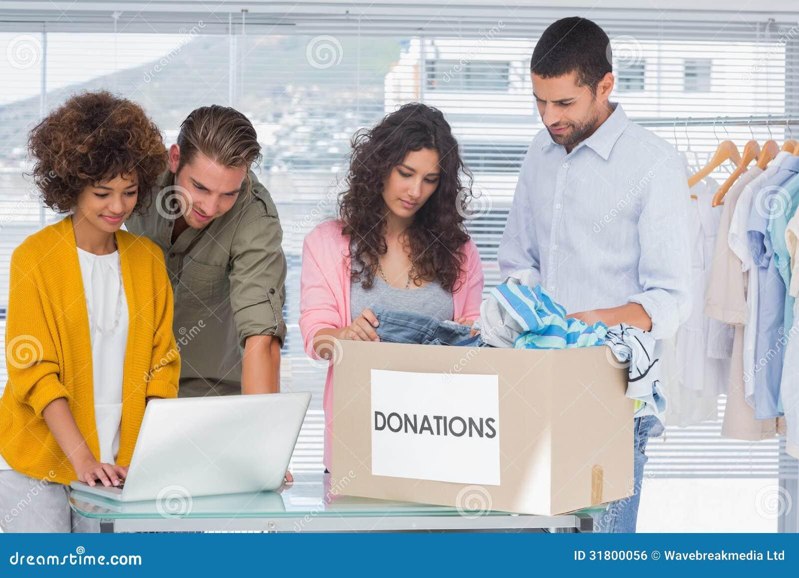 Volontärer som använder en bärbar dator och tar kläder från välgörenhet, boxas
