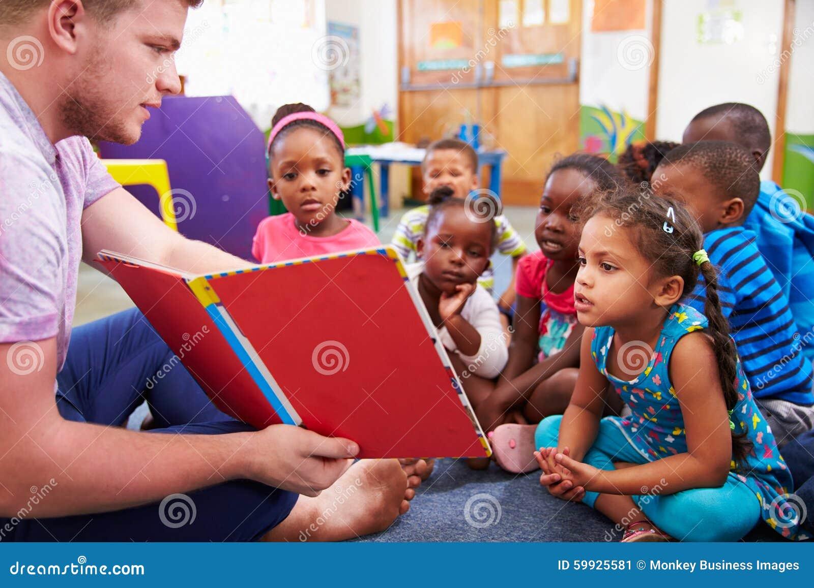 Volontärlärare som läser till en grupp av förskole- ungar