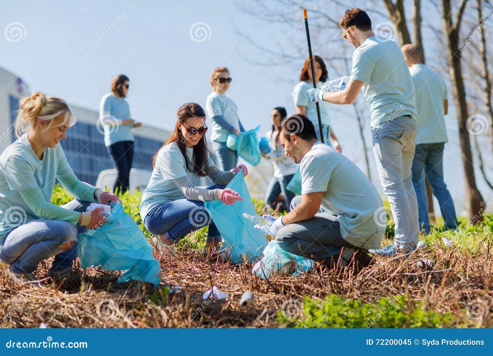 Volontaires avec des sacs de déchets nettoyant le secteur de parc