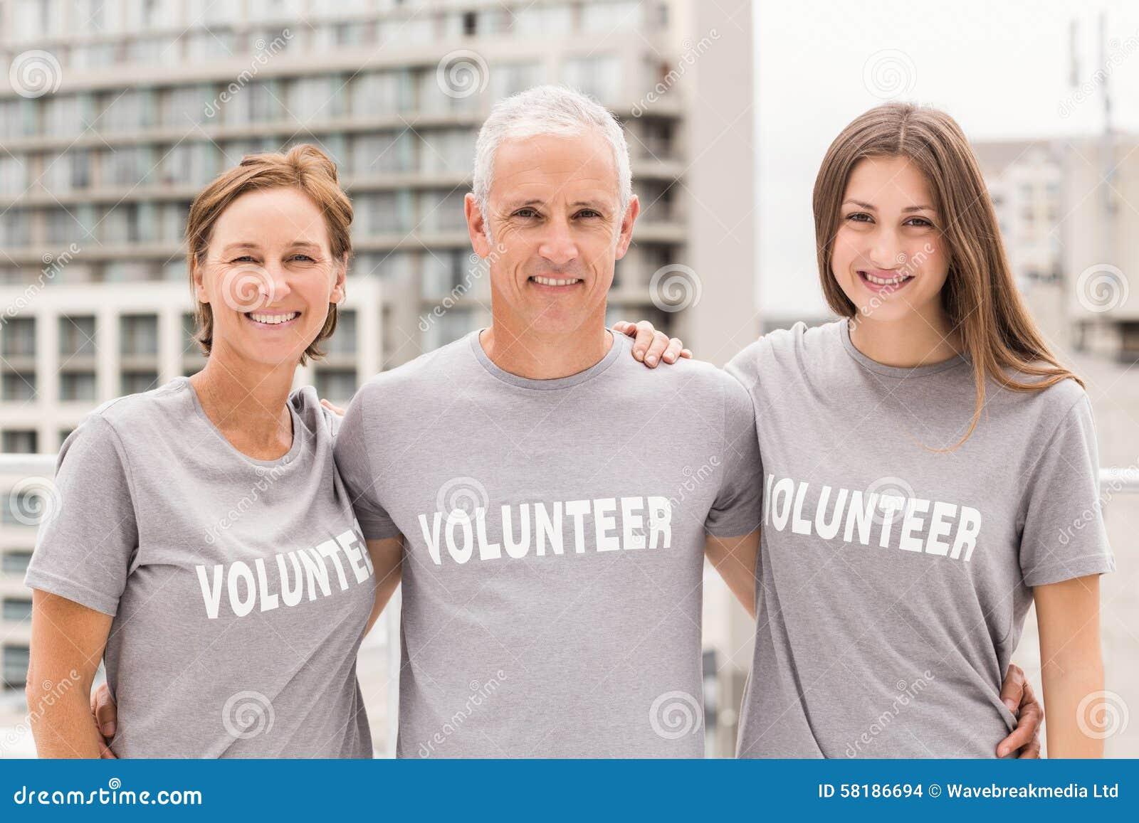 Volontari sorridenti che mettono armi intorno ad a vicenda