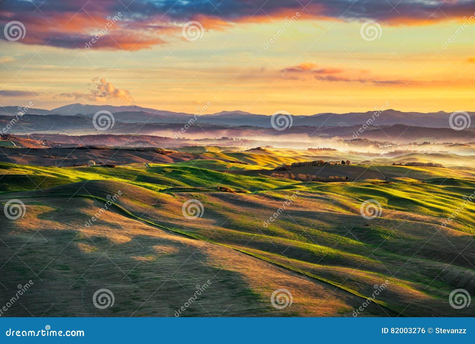 Volterra mgłowa panorama, toczni wzgórza i zieleni pola na sunse,