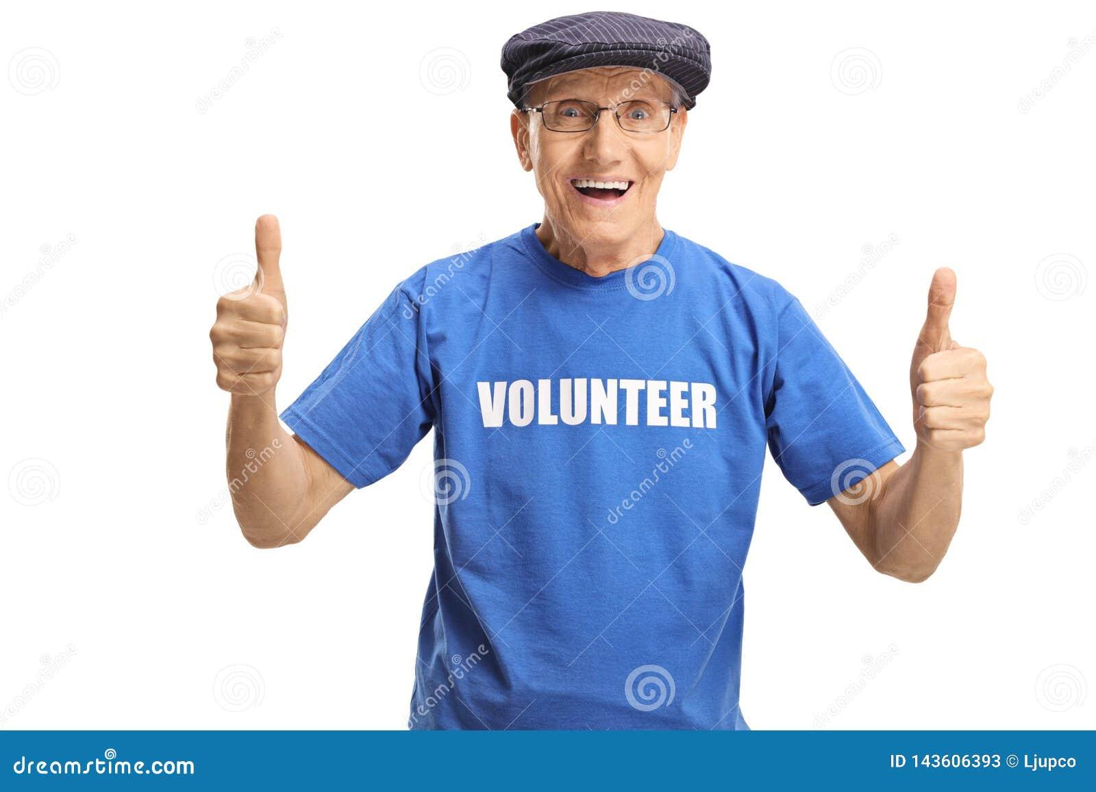 Voluntário masculino idoso alegre em um t-shirt azul que mostra os polegares acima