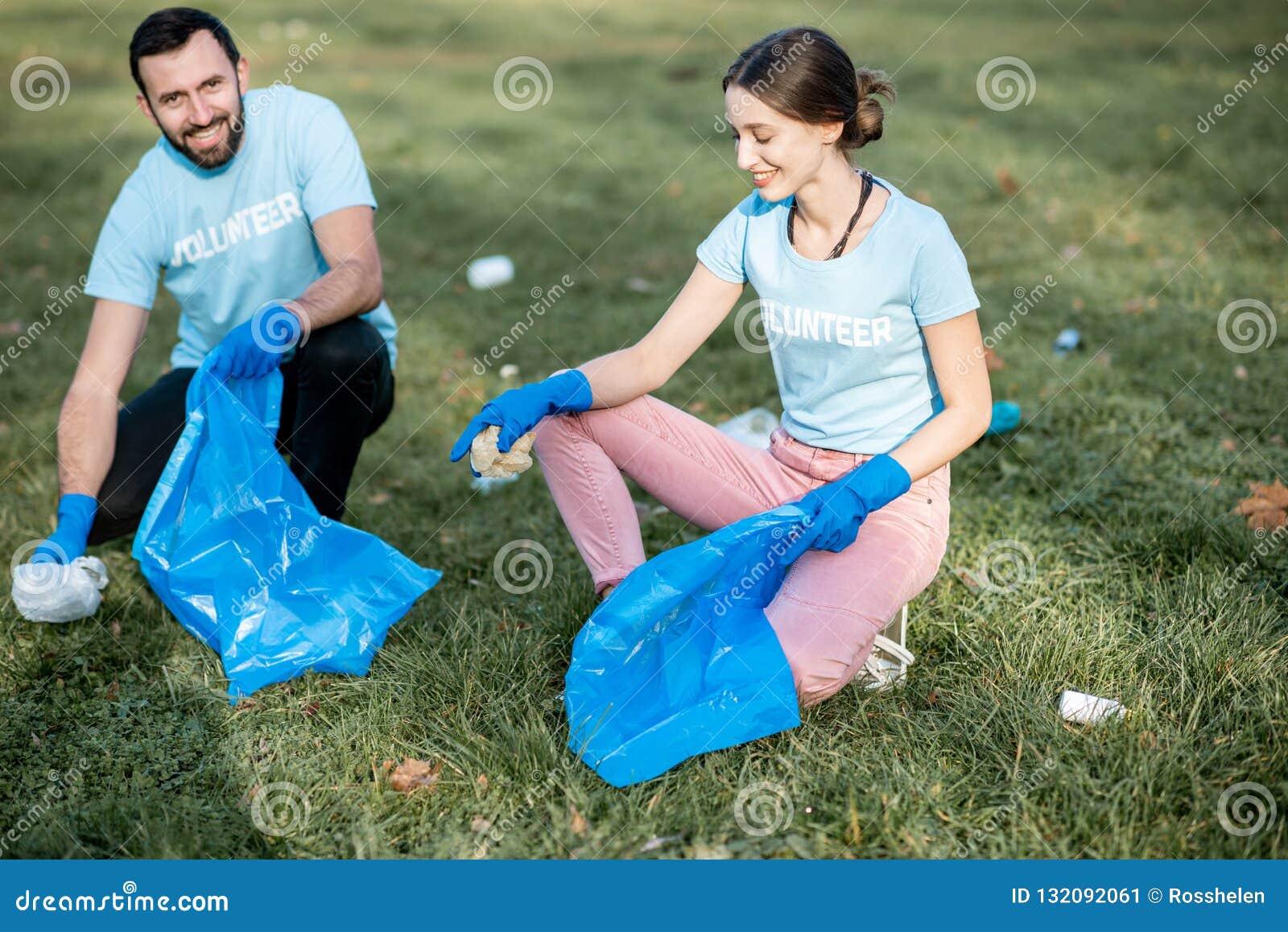 Voluntários que limpam o parque público dos desperdícios