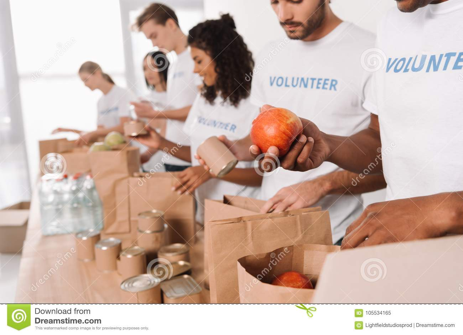 Voluntários que põem o alimento e as bebidas em sacos