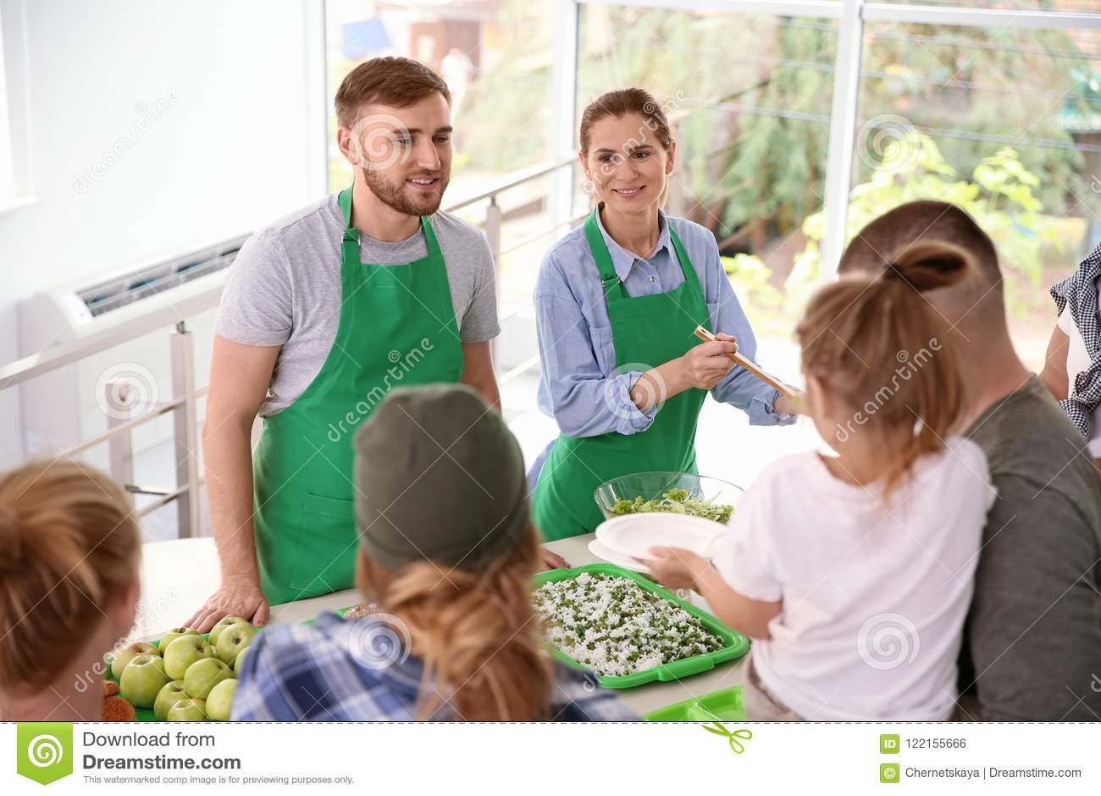 Voluntários que servem o alimento para povos pobres