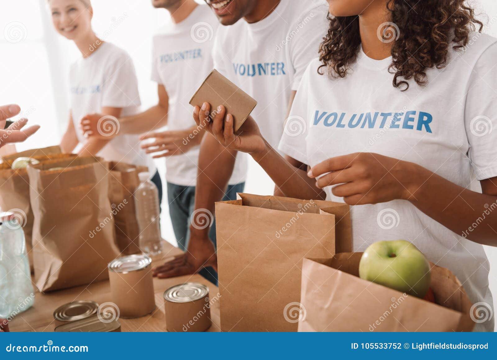 Voluntarios que embalan la comida y las bebidas para la caridad