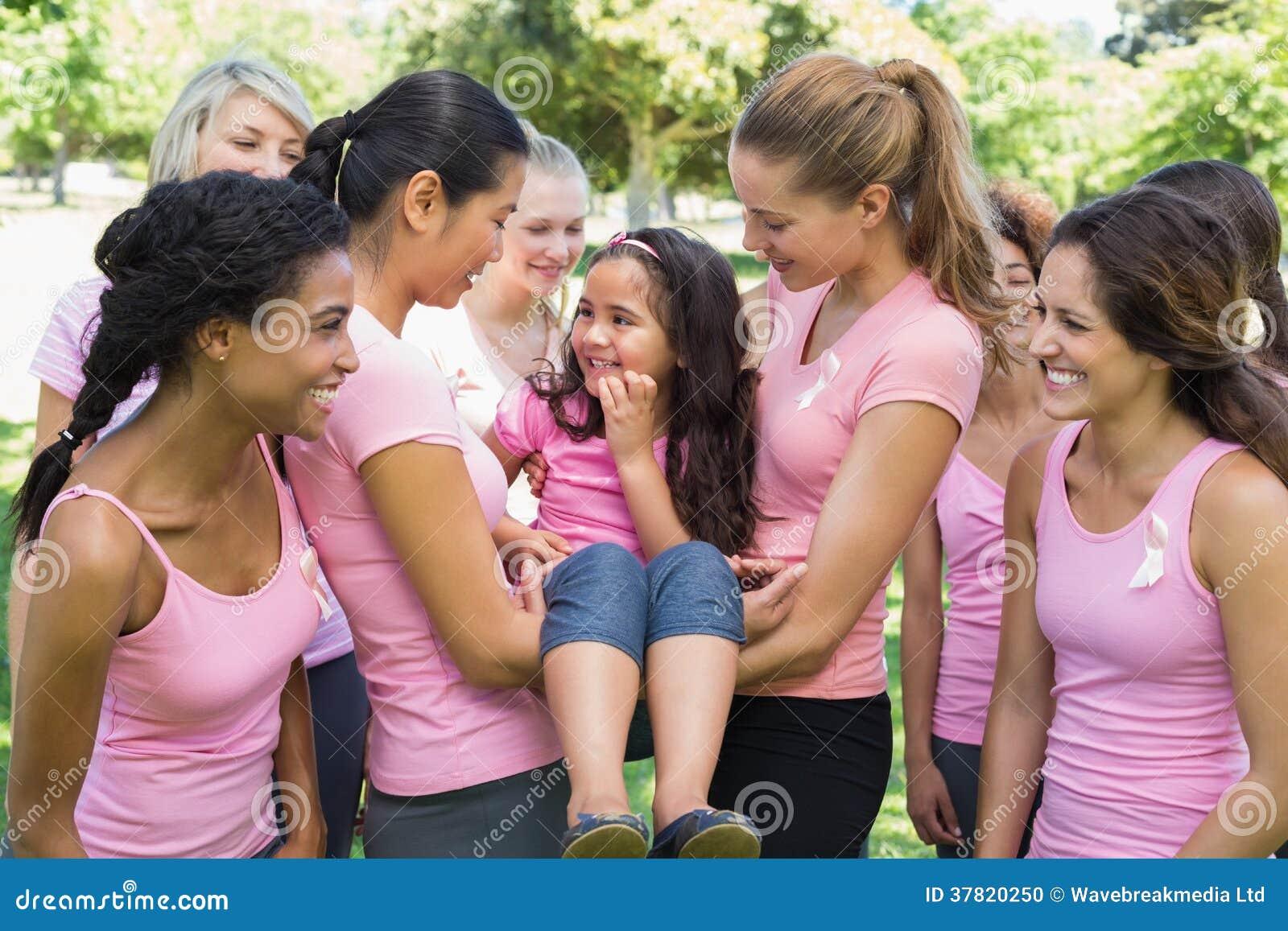 Voluntarios que llevan a la muchacha durante campaña del cáncer de pecho