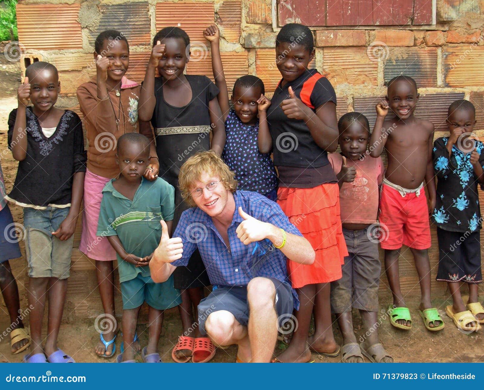 Volunteer aid relief worker having fun teaching African children thumbs up