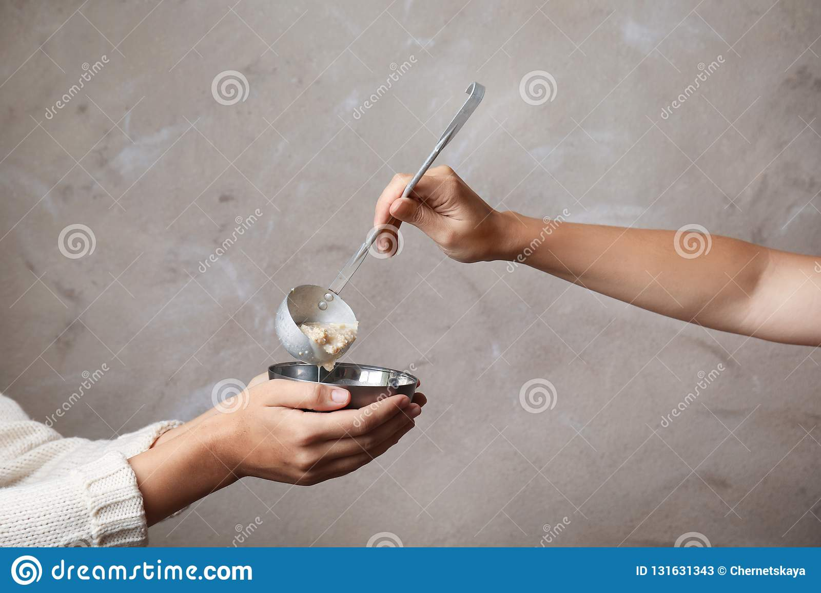 Volunteer putting food into bowl of poor woman on color background, closeup.
