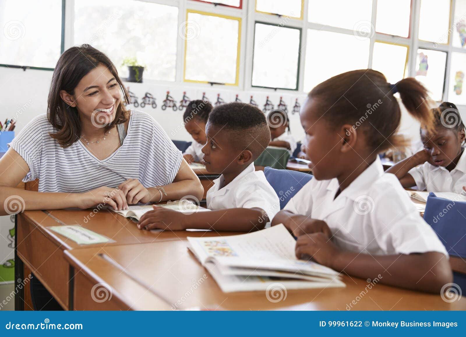 Volunteer teacher helping school kids in classroom, close up