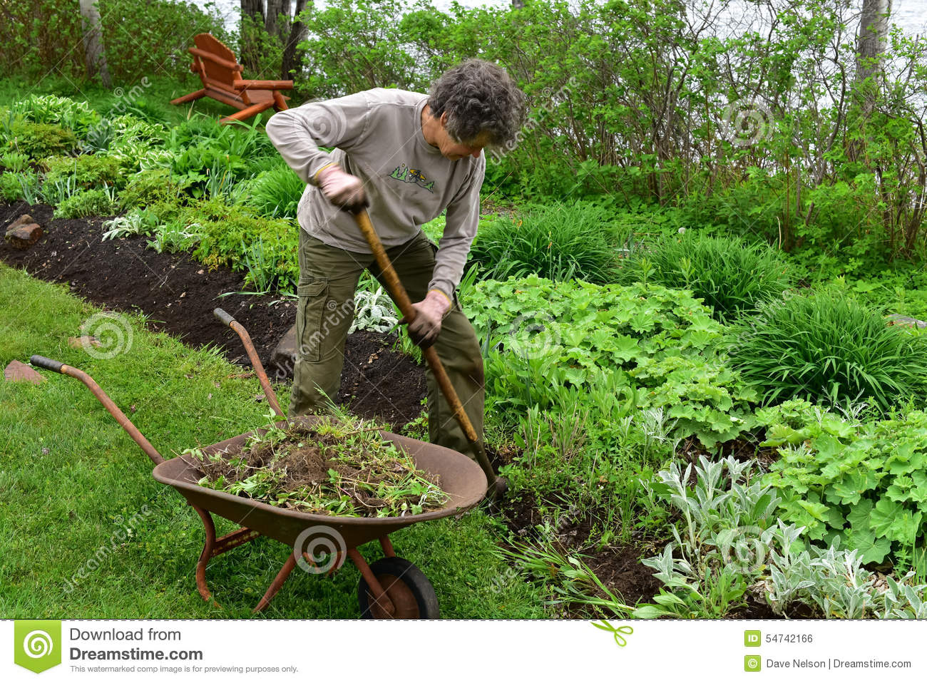 Volunteer Woman Gardener Digging In Flowerbed Stock Photo