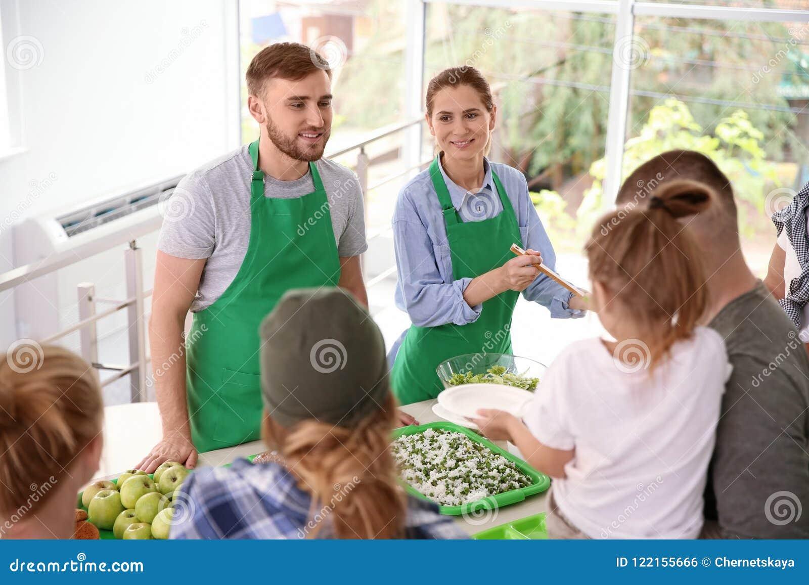 Volunteers serving food for poor people
