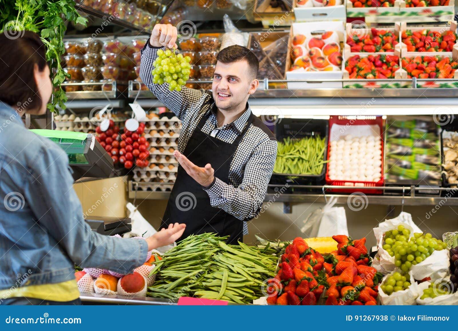 f2934e395b2fe8 De volwassen mensenverkoper die klant helpen om fruit en groenten in  kruidenierswinkel te kopen winkelt