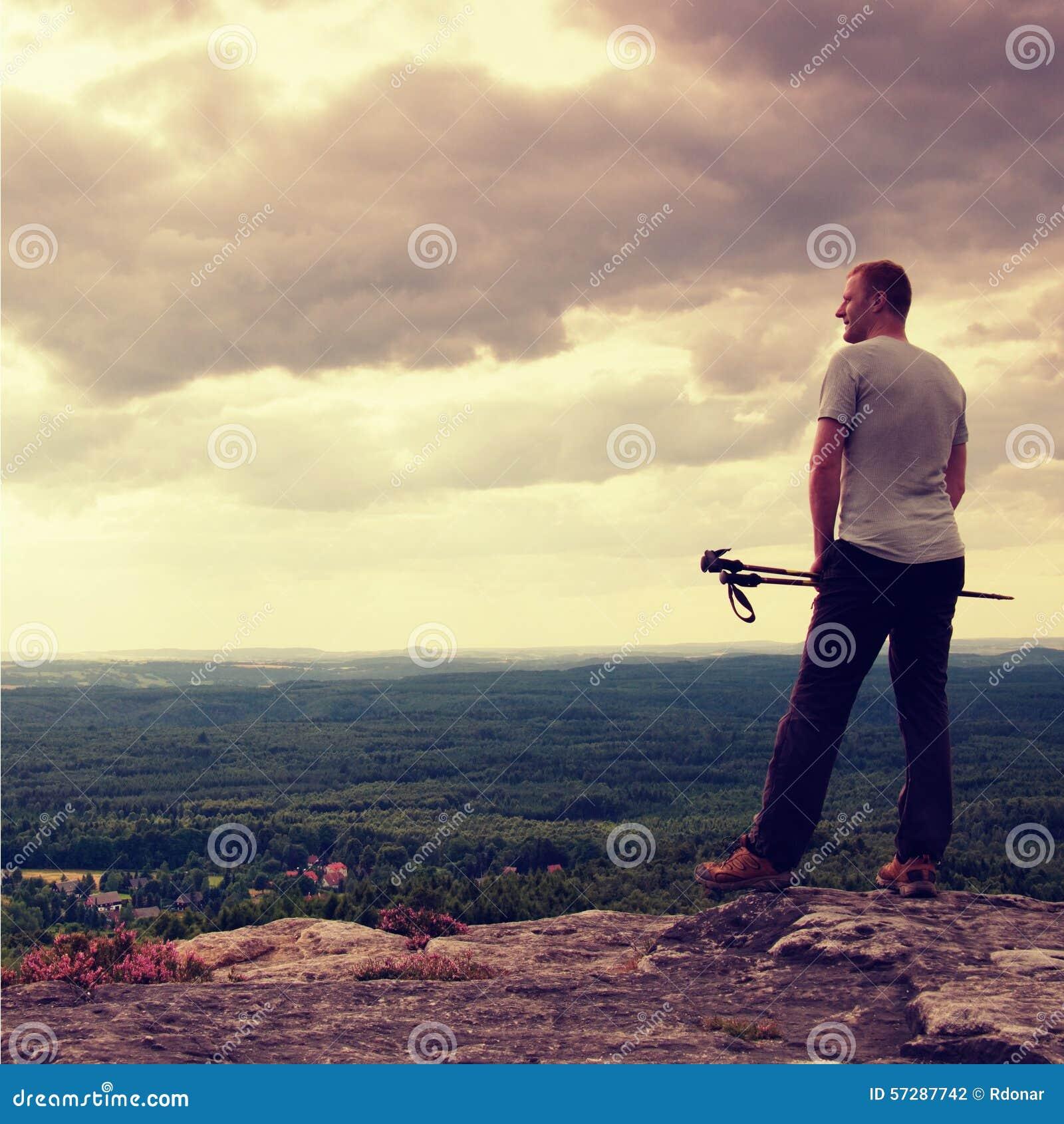 Volwassen wandelaar met in hand polen De wandelaar neemt een rust op rotsachtig meningspunt boven vallei Zonnige dag rotsachtige