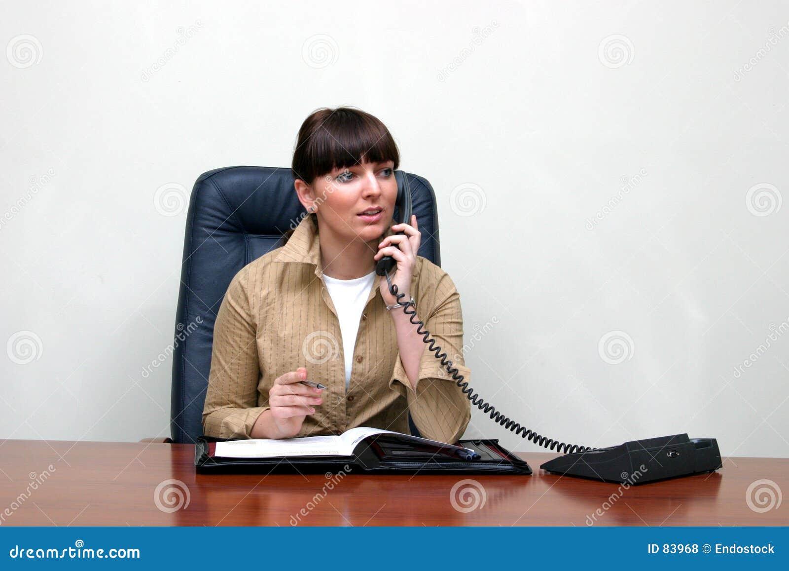 Volwassen witte vrouw achter een bureau in een bureau dat spreekt