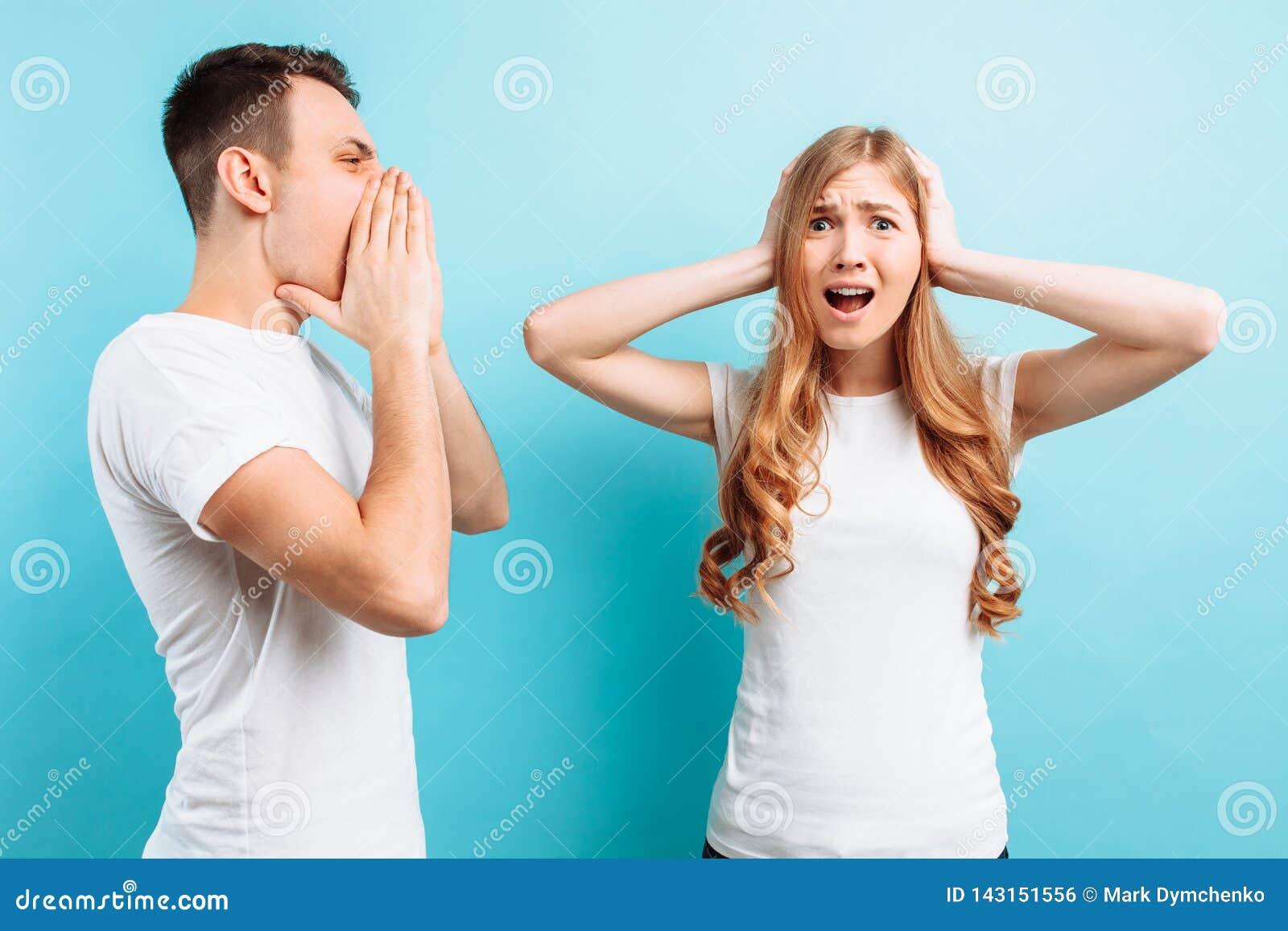 Von einem jungen, aggressiven Mann, der an einer Frau schreit, bedeckt eine Frau ihre Ohren mit seinen Händen, auf einem blauen H
