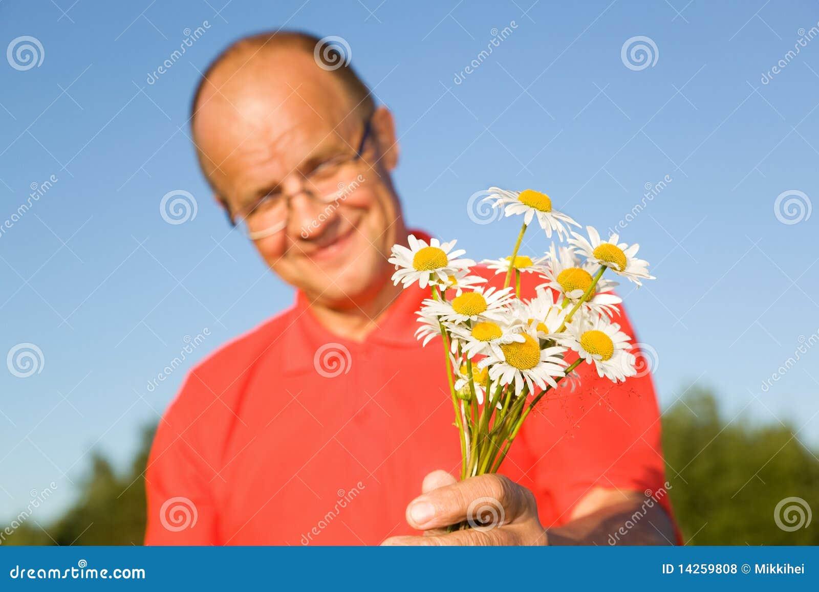 Von mittlerem Alter Mann, der Blumen gibt
