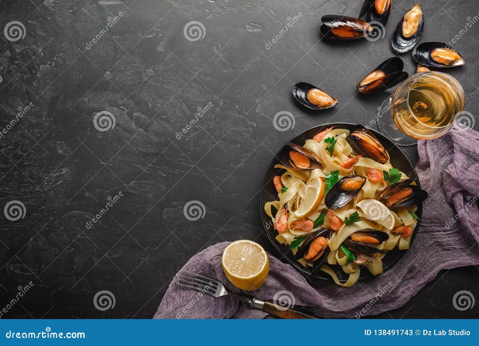 Vongole спагетти, итальянские макаронные изделия морепродуктов с clams и мидии, в плите с травами на деревенской каменной предпос