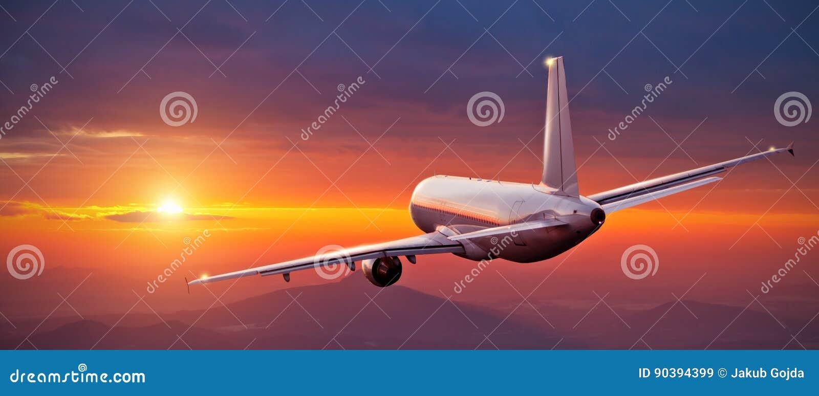 Voo comercial do avião acima das montanhas no por do sol