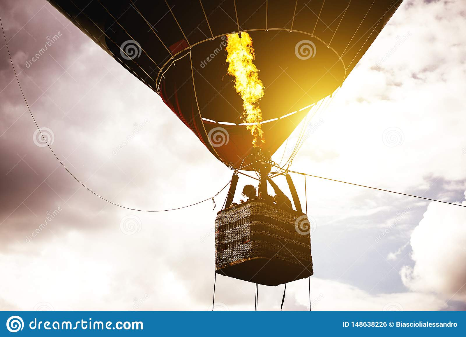 Voo do balão de ar quente em um céu nebuloso no nascer do sol - imagem do voo da silhueta do balão sobre o céu